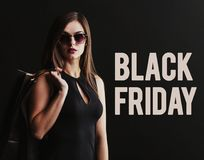 Black Friday Shopping. Elegant brunette woman wears sunglasses and black dress holding black shopping bags, black friday concept Royalty Free Stock Photos