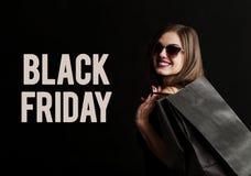 Black Friday Shopping. Elegant brunette woman wears sunglasses and black dress holding black shopping bags, black friday concept Royalty Free Stock Photo