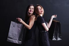 Black Friday Shopping. Elegant brunette womans wears black dress holding black shopping bags, black friday concept Stock Photos