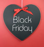 Black Friday shopping sale concept with message on a heart shape blackboard. Against a red background Royalty Free Stock Images