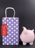 Black Friday shopping sale concept. With red ticket Sale tag on purple shopping bag with piggy bank Royalty Free Stock Photography
