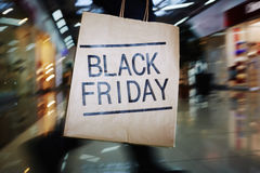 Black Friday shopping. Shopaholic with Black Friday paperbag moving in the mall Royalty Free Stock Photo