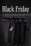 Black Friday sign.  A lot of  pants jeans and jacket hanging on clothes rack.  background. Black Friday sign.  A lot of black pants jeans and jacket hanging on Stock Images
