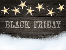 Black Friday sign on wooden background with star-shaped lights and snow. Design template for banners, flyers and so. Royalty Free Stock Image