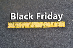 Black Friday Text on Asphalt Street. Black Friday words on asphalt paved street with yellow painted line Royalty Free Stock Image