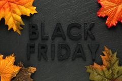Black Friday text with autumn leaves on black slate. Background Royalty Free Stock Photos