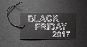 Black Friday 2017 text on a black tag. On black paper background Stock Image