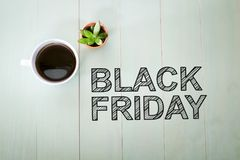 Black Friday text with a cup of coffee. On pastel green wooden table stock photo