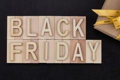 Black Friday - Text in den hölzernen Buchstaben auf Tafel mit Geschenk Lizenzfreie Stockfotografie