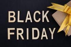 Black Friday - Text in den hölzernen Buchstaben auf Tafel mit Geschenk Stockbild