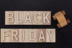 Black Friday - Text in den hölzernen Buchstaben auf Tafel mit hölzernem Stockfotografie