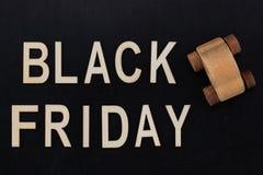 Black Friday - Text in den hölzernen Buchstaben auf Tafel mit hölzernem Lizenzfreie Stockfotos