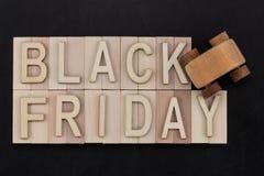 Black Friday - Text in den hölzernen Buchstaben auf Tafel mit hölzernem Stockfotos