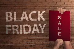 Black Friday text with hand holding sale banner. Against wall background Stock Images