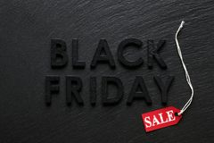 Black Friday text with red sale tag on slate. Background Royalty Free Stock Photography