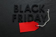 Black Friday text with red sale tag on slate. Background Stock Photos