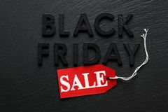Black Friday text with red sale tag on slate. Background Stock Photo