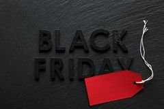 Black Friday text with red sale tag on slate. Background Royalty Free Stock Photo