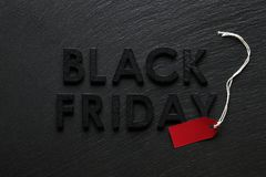 Black Friday text with red sale tag on slate. Background Stock Image