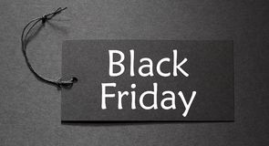 Black Friday text on a black tag. On black paper background stock photography