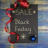 Black Friday-Verkauf geschrieben auf schwarze Karte mit rotem Weihnachtsband Stockfoto