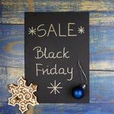 Black Friday-Verkauf geschrieben auf schwarze Karte mit Weihnachtsflitter und -lebkuchen Stockbilder