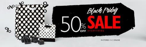 Black Friday-verkoopbanner, met kleine zwarte gift-dozen, en zwart-witte gift-zakken met stippen Stock Foto