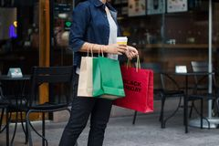 Black friday. Woman with coffee cup holding shopping bags stock photography