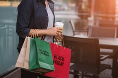 Black Friday, Woman with coffee cup holding shopping bags stock photography