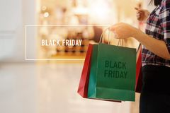 Black Friday, Woman holding shopping bags walking in mall stock image