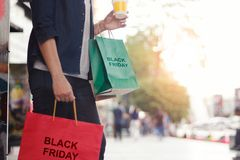 Black Friday, Woman with coffee cup holding shopping bags royalty free stock images