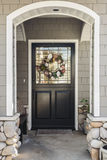 Black front door of a home seen through an arch. A black front door with a wreath to a gray home, viewed through a white arch. The house has gray shingles. Also Royalty Free Stock Photos