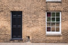 Black front door on a restored brick wall of a Victorian house r royalty free stock photo