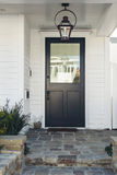 Black front door of white home royalty free stock photos