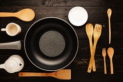 Black frying pan with cooking utensils on black wood table backg. Round Stock Images