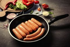 Black frying pan with delicious grilled sausages. On kitchen table stock photo
