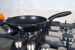 Black frying pan on a plate stock photos