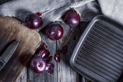 Black frying pan and a red onion on a gray wooden surface Stock Image