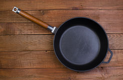 Black frying pan on a wooden background Royalty Free Stock Images