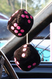 Black Fuzzy Dice. A set of black fuzzy dice with hot pink dots hands on a classic car mirror stock image