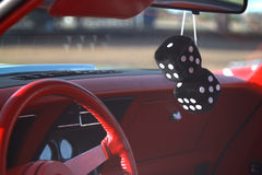 Black fuzzy dice hanging from the rear view mirror Royalty Free Stock Images