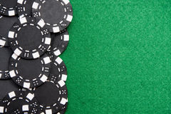 Black gambling chips on green felt background with royalty free stock photo