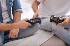 Black game consoles in hands of two men Royalty Free Stock Photography