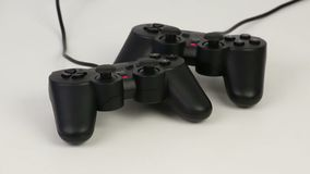 Gamepads on a white background rotates. Black gamepads on a white background rotates stock video footage