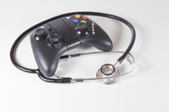 Black gaming controller and doctors stethoscope royalty free stock image