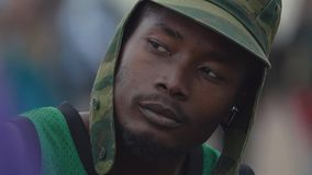 Black gang member young man listening music in headphones. Black gang member young man in camouflage cap, green basketball shirt listening music in headphones at stock video footage