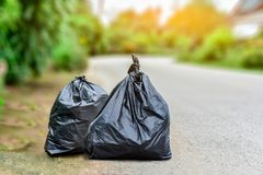Black garbage waste food. Black garbage bag on floor of road waiting bring to dispose Stock Photo
