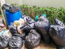Black garbage bag pile near municipal trash bin full on sidewalk royalty free stock images