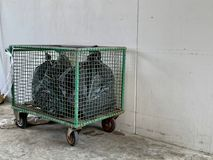Black garbage bags arranged in a green cart on the cement floor beside the white wall, Garbage cart for recycling royalty free stock image