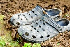 Black garden shoes of crocs style. Black garden muddy shoes of crocs style royalty free stock images